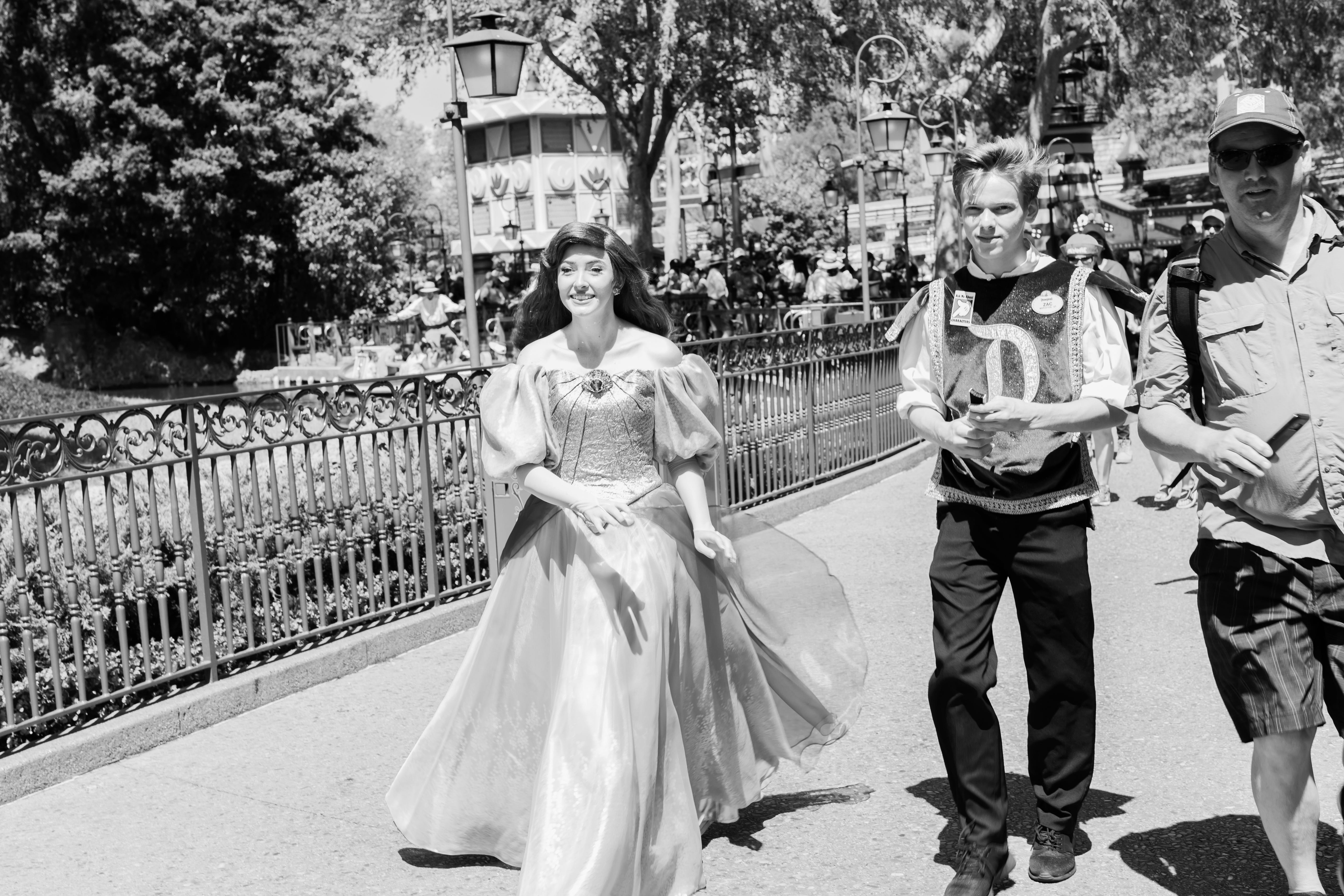 A Disneyland cast member dressed as Ariel, from The Little Mermaid, walks through the park.