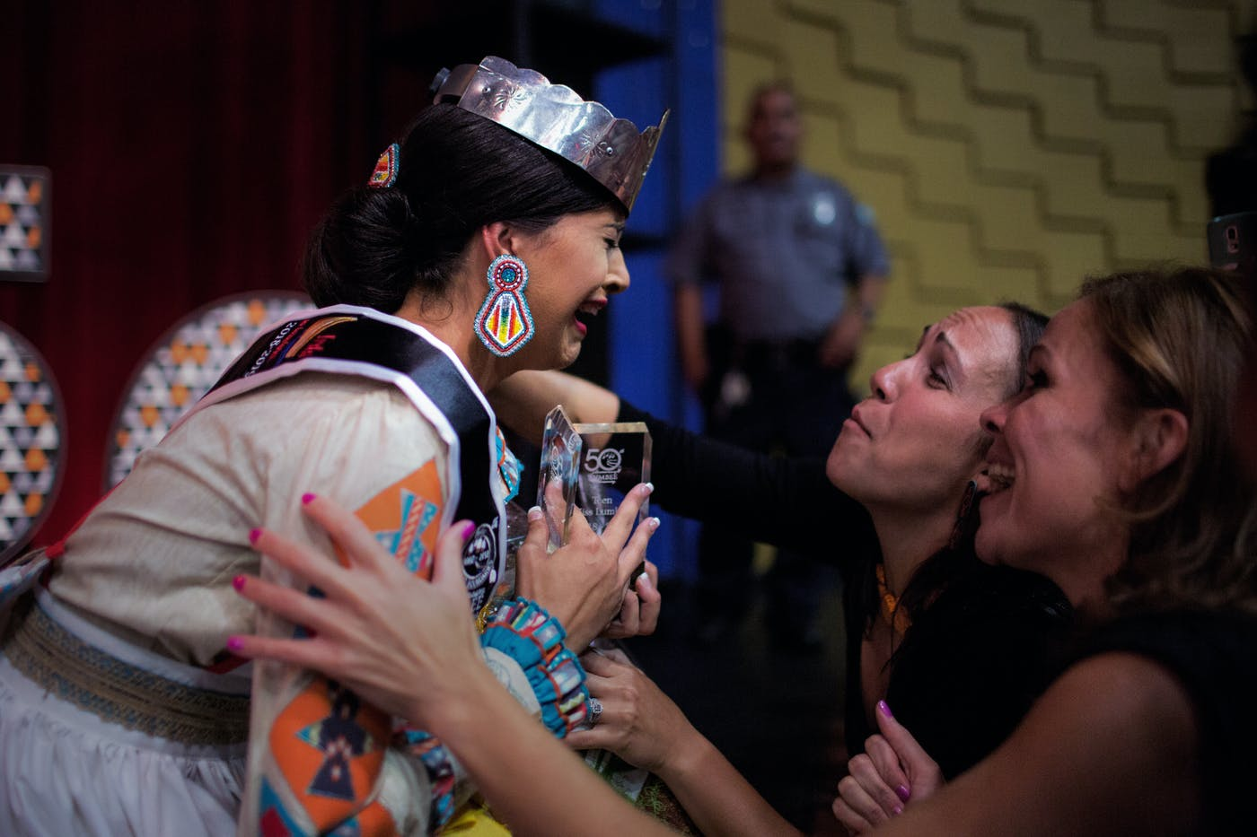 Teen Miss Lumbee winner Jacobs kneels at the edge of the stage after she's pronounced the winner.