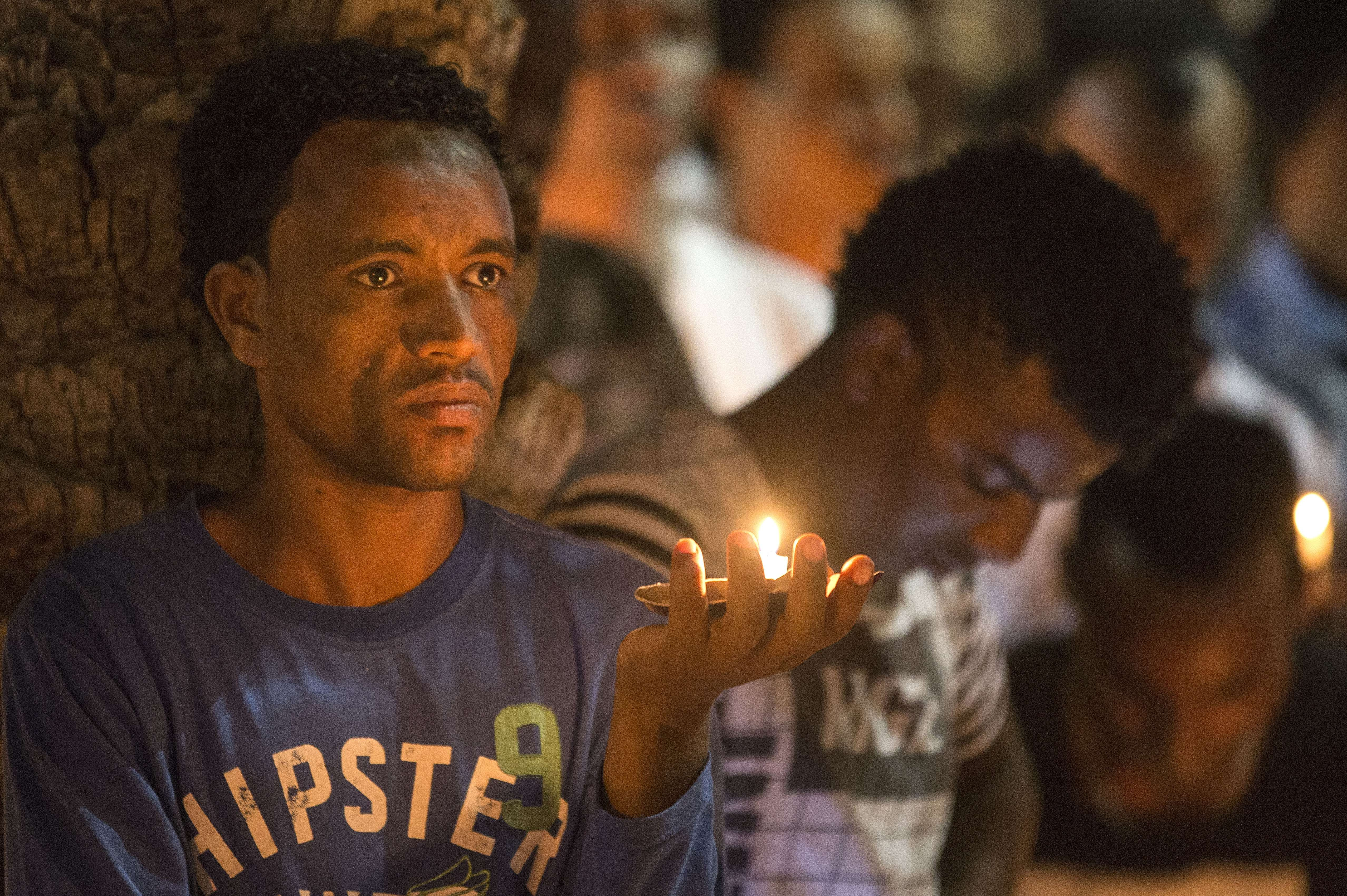 A member of the Eritrean community in Israel holds a candle on October 21, 2015 in the Israeli city of Tel Aviv during a memorial ceremony for Eritrean asylum seeker Haptom Zerhum.