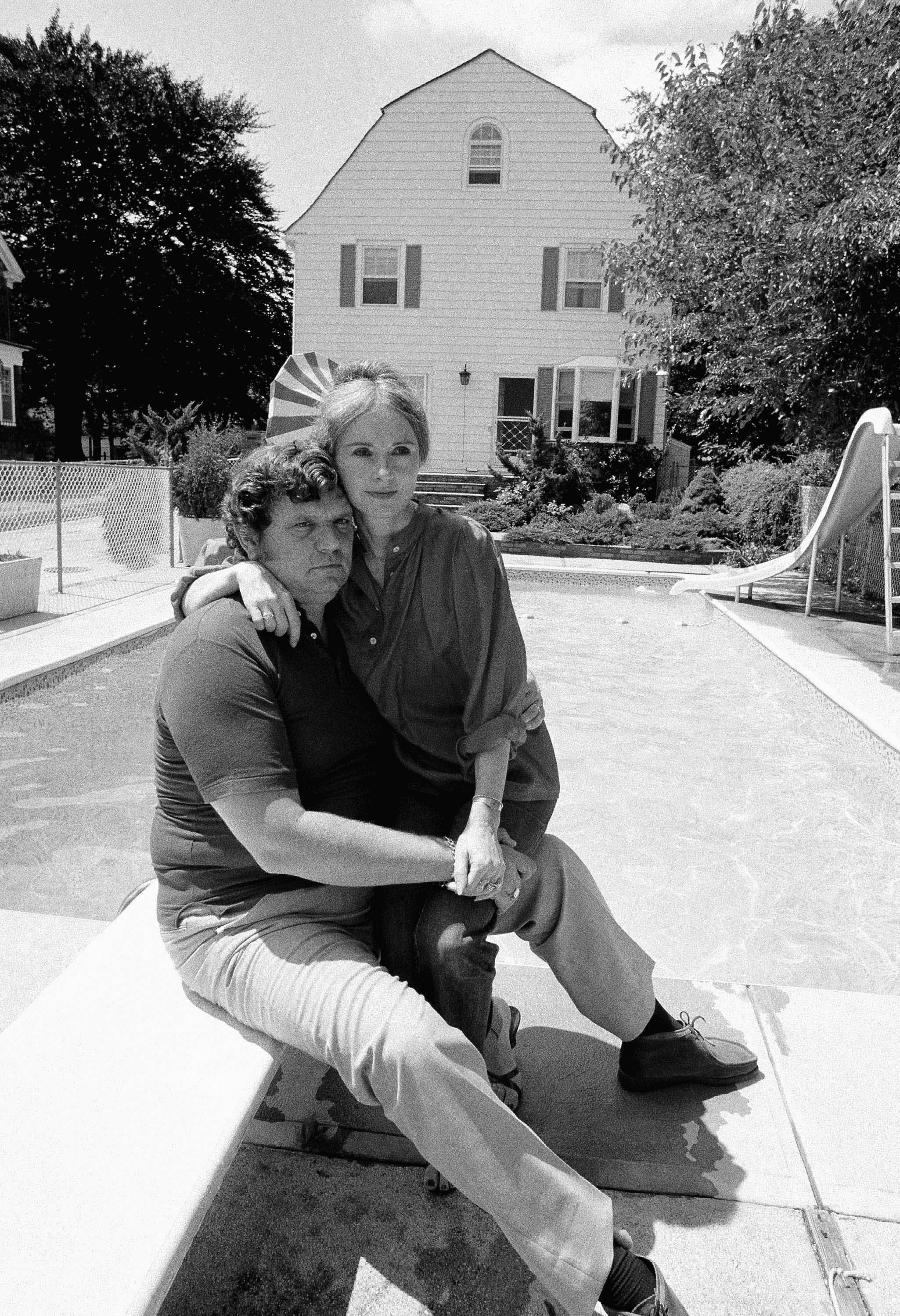 Jim and Barbara Cromarty pose near pool of their Amityville home in 1979. The couple opened their home to newsmen to disprove stories about eerie happenings at the house where the Defeo family was slain years ago. (AP Photo/Dan Grossi)