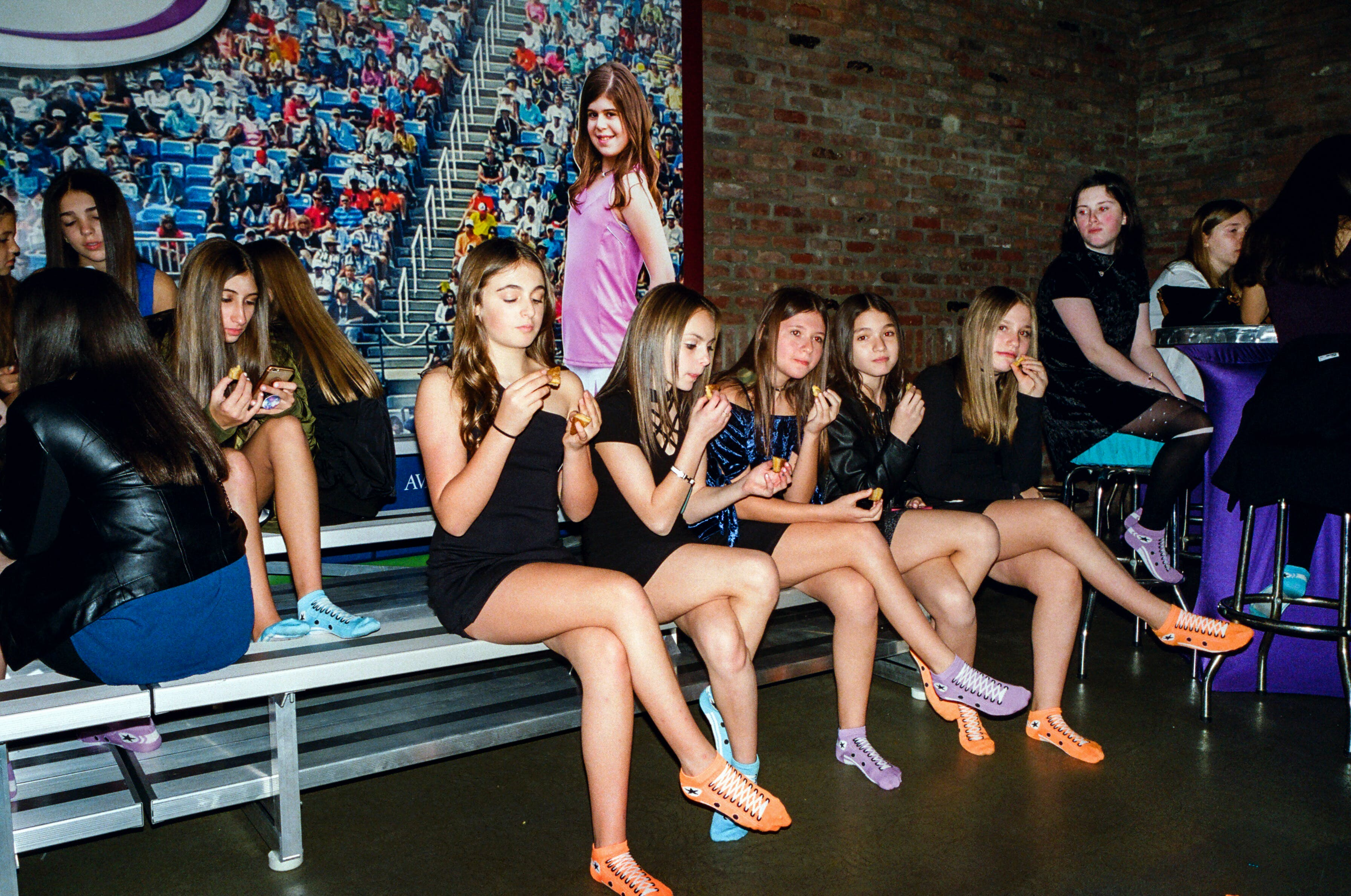 A braid of girls takes a breather on the bleachers.